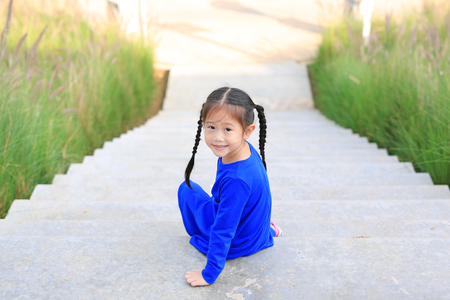 Adorable little Asian child girl sitting on stair in the garden with looking camera.