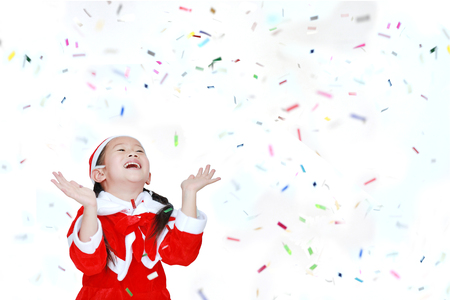 Happy child girl in Santa costume dress with colorful confetti ribbon paper thrown on white background. Merry Christmas and Happy New Year Concept. Stock Photo