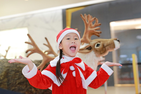 Happy little child girl in santa costume dress on winter time against reindeer christmas background.  Merry Christmas and happy new year.