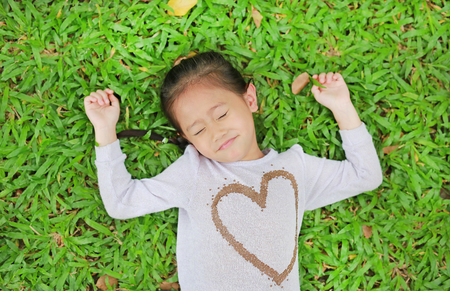 Happy cute little Asian child girl lying on green lawn. Smiling and closed her eyes. Banque d'images
