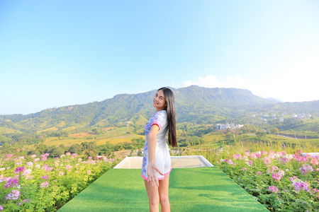 Half length of young Asian woman feeling free with arms wide open at beautiful trees and mountains on blue sky with morning sunlight. Imagens