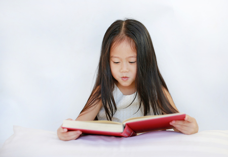Beautiful little Asian child girl reading hardcover book lying with pillow on white background. Stock fotó