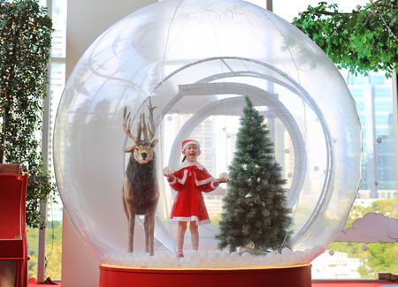 Happy little Asian child girl in santa costume dress playing in big winter Snow globe with reindeer on christmas time. Merry Xmas and happy new year. Stockfoto