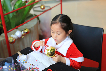 Cute little child girl making Christmas ball decoration ornament . Handmade New Year decorations.
