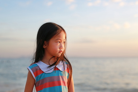 Peaceful little child girl standing on beach at sunset light with looking out.