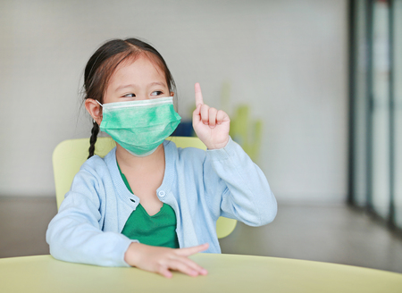 Cute little Asian child girl wearing a protective mask with showing one forefinger sitting on kid chair in children room. Foto de archivo