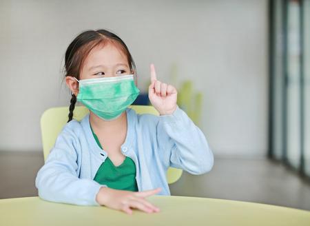 Schattig klein Aziatisch kindmeisje dat een beschermend masker draagt met een wijsvinger die op een kinderstoel in de kinderkamer zit. Stockfoto