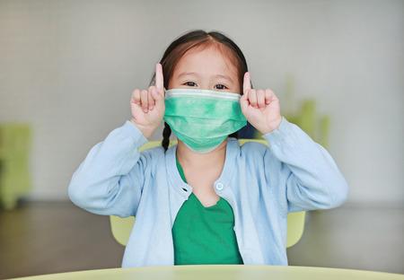 Süßes kleines asiatisches Mädchen, das eine Schutzmaske trägt und zwei Zeigefinger zeigt, die auf einem Kinderstuhl im Kinderzimmer sitzen.