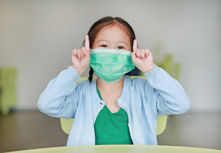 Cute little Asian child girl wearing a protective mask with showing two forefingers sitting on kid chair in children room.