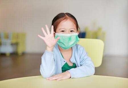 Simpatica bambina asiatica che indossa una maschera protettiva con cinque dita sedute su una sedia per bambini nella stanza dei bambini. Archivio Fotografico