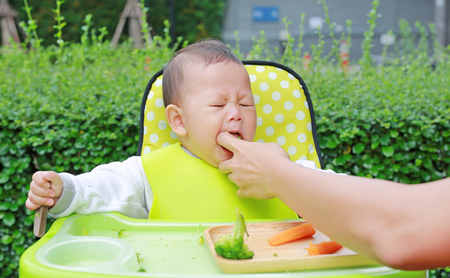 Close-up infant baby boy sitting on kid chair eating with something stuck in his mouth and mother help to keep out. Standard-Bild