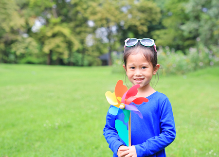 Happy asian child girl with wind turbine in the garden