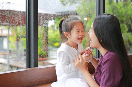 Asian mother and her daughter playing with love near a window while raining day.