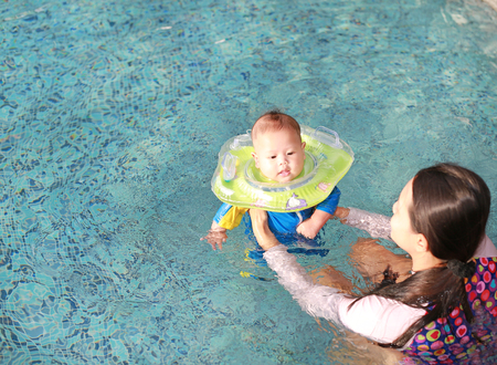Asian Mother training for infant baby boy in swimming suit floating in pool with safety by baby neck floats.