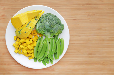Fresh vegetable on white plate against wooden background with copy space (broccoli, pumpkin and sweet pea)