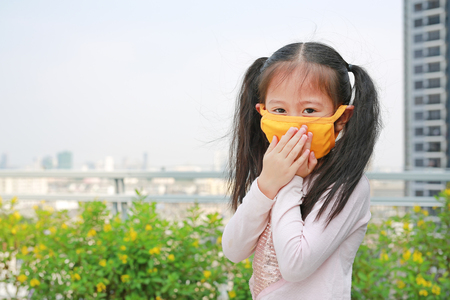 little child girl wearing a protection mask against PM 2.5 air pollution in Bangkok city. Thailand. Stockfoto