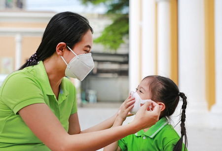 Asian young mother wearing protective mask for her daughter while outside to against PM 2.5 air pollution in Bangkok city. Thailand.