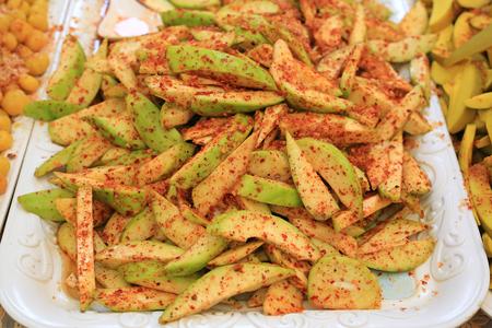 Conserver la mangue épicée, saupoudrer de sucre, de poudre de chili et de sel