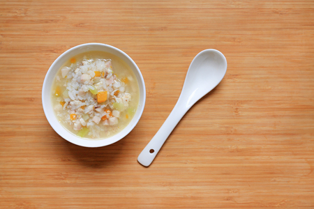 Porridge for baby food in white ceramic bowl and spoon on wood board background.
