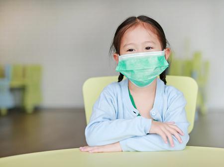 Nettes kleines asiatisches Kindermädchen, das eine Schutzmaske trägt, die auf einem Kinderstuhl im Kinderzimmer sitzt.