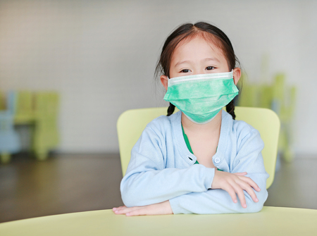 Cute little Asian child girl wearing a protective mask sitting on kid chair in children room.