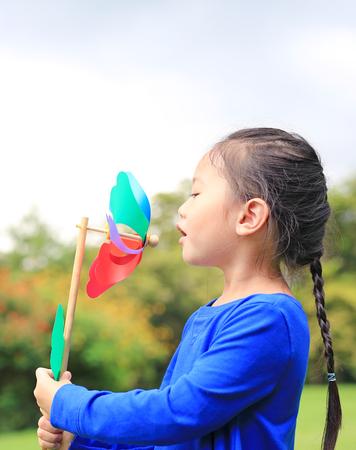 Adorable little Asian kid girl blowing wind turbine in the summer garden.