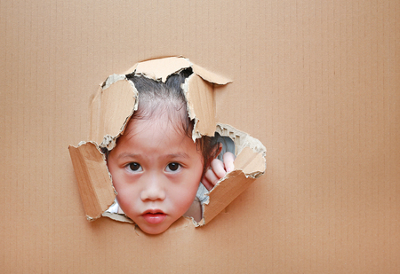 Adorable little Asian child girl looking through hole on cardboard.
