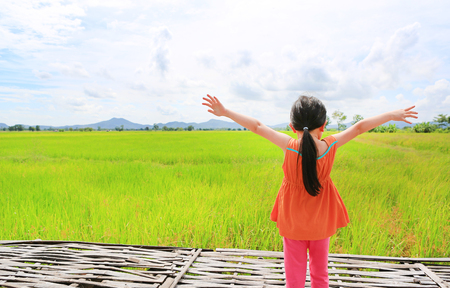 Rear view of little Asian child girl stretch arms and relaxed at the young green paddy fields Banque d'images