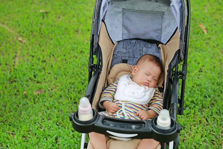 Closeup Asian newborn baby boy sleeping in stroller on nature park.