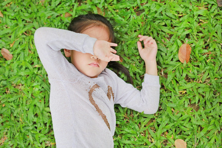 Portrait of beautiful little Asian child girl lying on green grass lawn closed her eyes with her hands.
