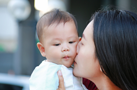 Close-up Asian mother kissing her infant. Happy family.