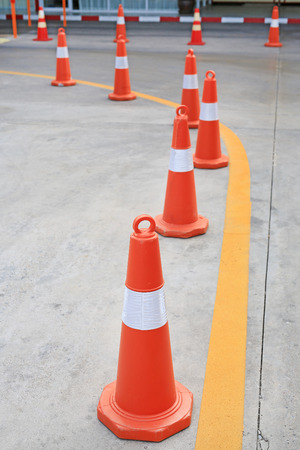 Row of orange rubber traffic cone placed in road. Banque d'images