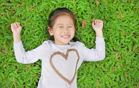 Portrait of smiling cute little Asian child girl lying on green lawn.
