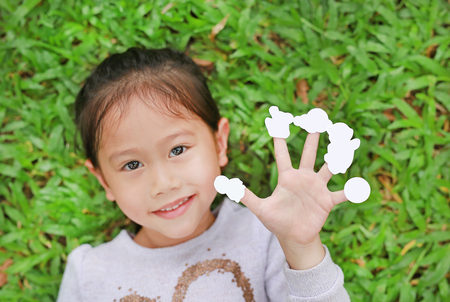 Cute little Asian kid girl lying on green grass lawn with showing empty white stickers on her fingers. Focus on hand.