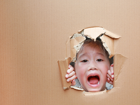 Happy Asian kid girl looking up from hole on cardboard with copy space. Imagens