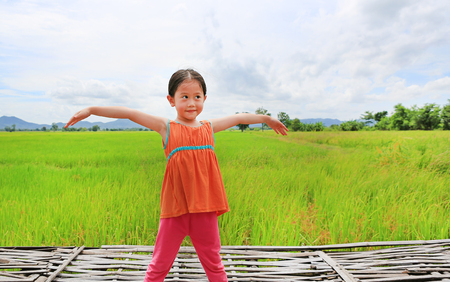 Asian kid girl stretch arms and relaxed at the young green paddy fields with looking up.