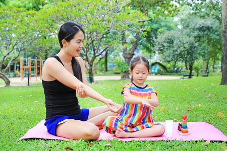 Mutter, die im Sommerpark Körperlotion für die Tochter anwendet.
