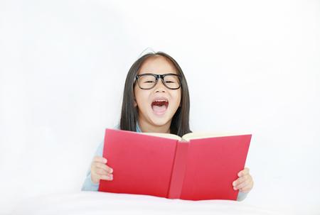 Smiling little Asian kid girl wearing glasses reading hardcover book lying on bed against white background. Banco de Imagens