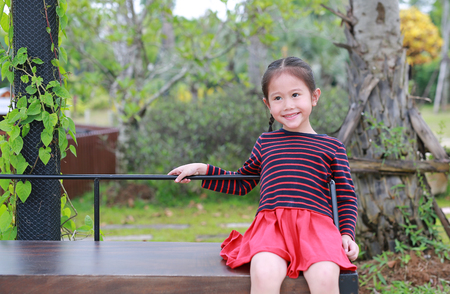 Happy little Asian child girl sitting on wood bench in the public garden. Banque d'images