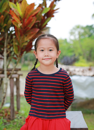 smiling little Asian child girl looking at you in the garden outdoor. Banco de Imagens