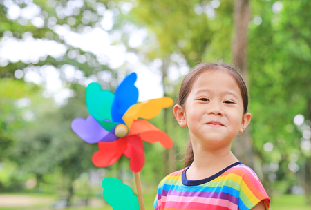 Close up cute little Asian child girl with wind turbine in the garden