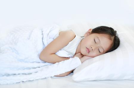 Sleeping beautiful Asian child girl lying on bed.