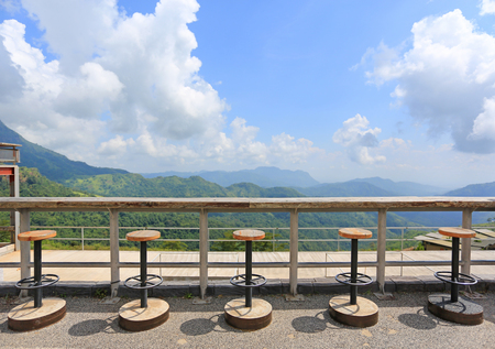 Row of stools at landscape viewpoint of terrace at sunny day with cloud and blue sky.