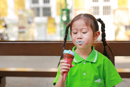 Happy little Asian kid girl enjoy eating ice cream cone with stains around her mouth.