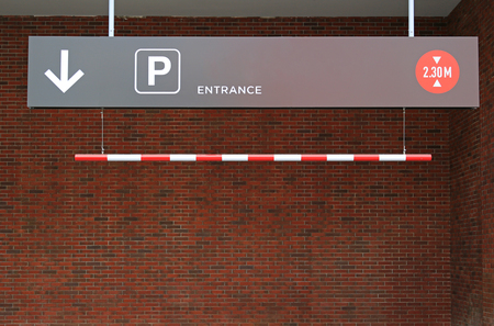 Car park entrance to a parking lot with signs arrow and height limit 2.30 m.