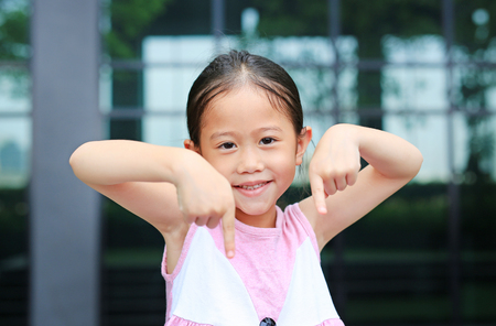 Asian little girl posture pointing her forefinger down with little smile.