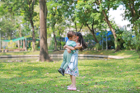 Asian sister carrying her little brother in the garden outdoor.