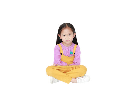 Portrait of angry little Asian child girl in pink-yellow pink-yellow dungarees sitting isolated on white background with copy space.