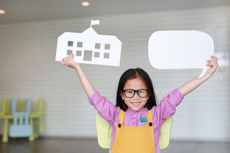 Happy Asian little girl in pink-yellow dungarees holding mock-up paper school and empty blank speech bubble to tell something in classroom with looking straight. Education and conversation concept. Imagens