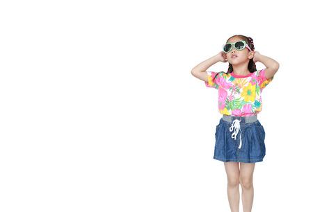 Cute little azjatyckie dziecko dziewczyna na sobie letnią sukienkę kwiaty i okulary przeciwsłoneczne na białym tle. Gotowy na letnie wakacje. Zdjęcie Seryjne
